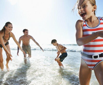 Parents playing on beach with two children (7-9, 10-12)