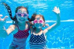Two little girls deftly swim underwater in pool