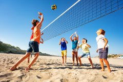 Big group of teenage boys and girls playing volleyball on the beach