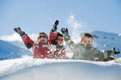 Italy, South Tyrol, Seiseralm, Children throwing snow in the air