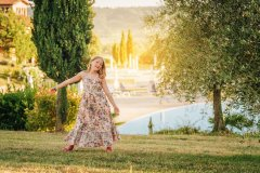 Outdoor portrait of adorable little girl wearing light dress, playing next to olive tree, summer vacation in Tuscany, Italy