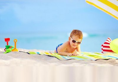 cute kid in sunglasses resting on colorful beach