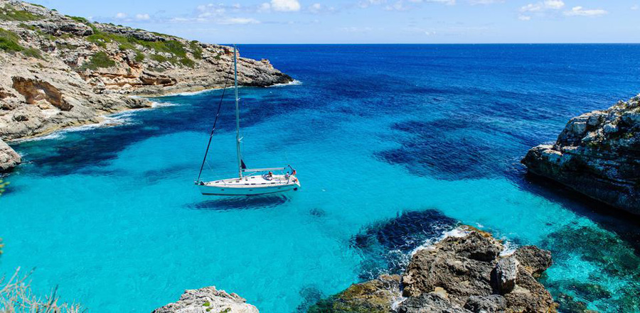 Sailing boat at anchor Paradise wild bay Cala Marmolis